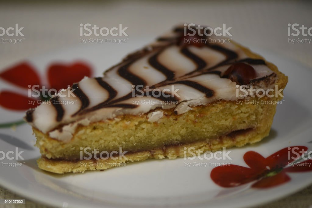 food photography of a close up sliced piece of delicious home made Bakewell tart or cake with jam and white icing with chocolate topping served on a floral pattern plate stock photo