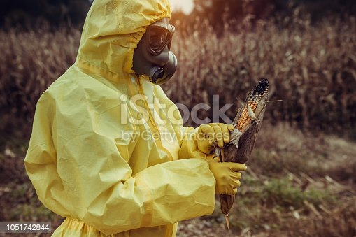 Scientist wearing protective suit and gas mask. Air pollution, GMO food concept.