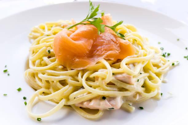 speisen  - spaghetti mit lachs stock-fotos und bilder