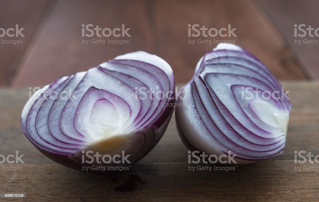 Food preparation, cooking concept: chopped and peeled fresh red onions on rustic wooden background stock photo