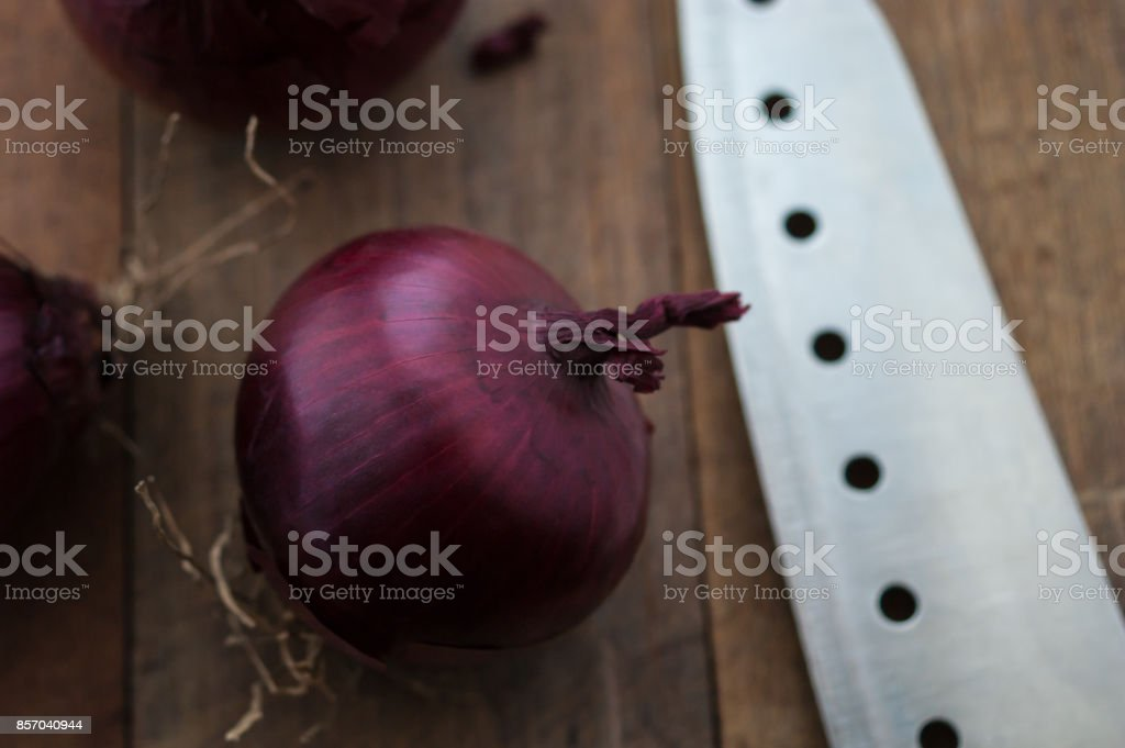 Food preparation, cooking concept: fresh raw red onions, knife on a rustic wooden cutting board background stock photo