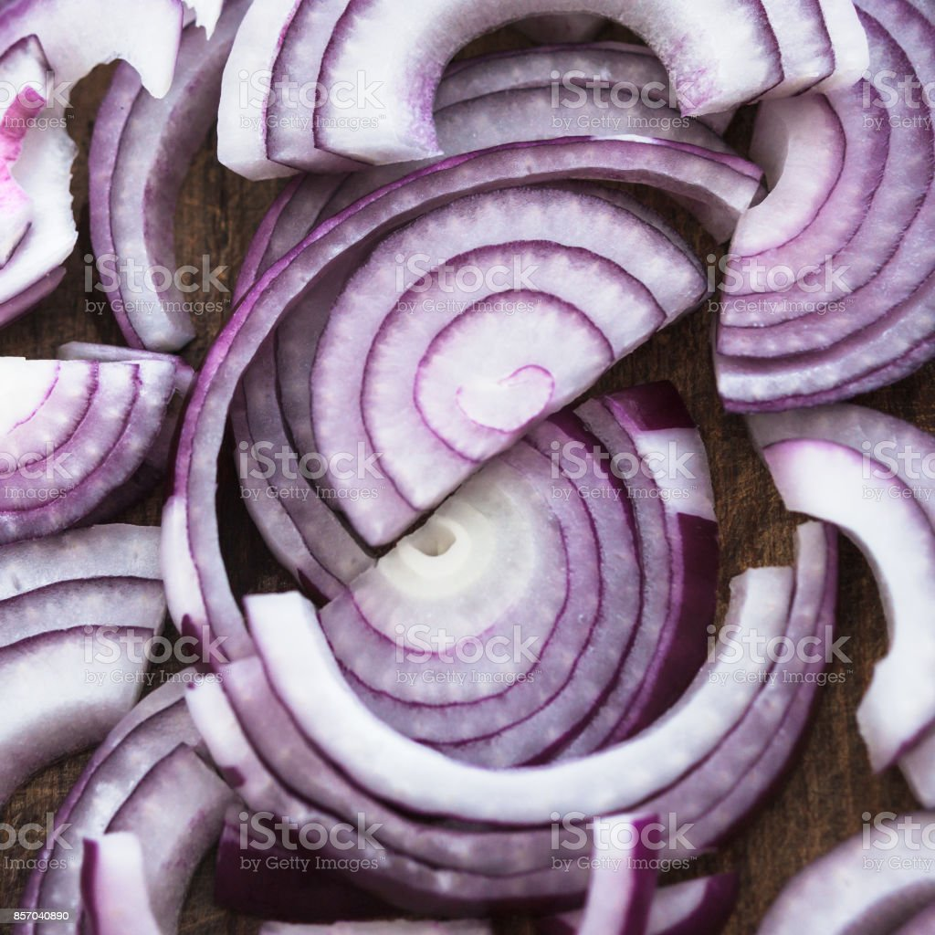 Food preparation, cooking concept: pattern of sliced fresh red onions on rustic wooden background stock photo