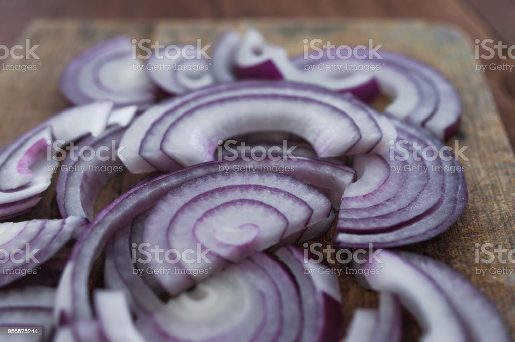 Food preparation, cooking concept: sliced fresh red onions on rustic wooden background stock photo