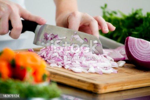 A chef cutting a red onion on a cutting board.