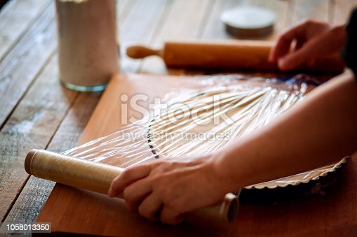 istock Food preserving using plastic wrap, close up 1058013350