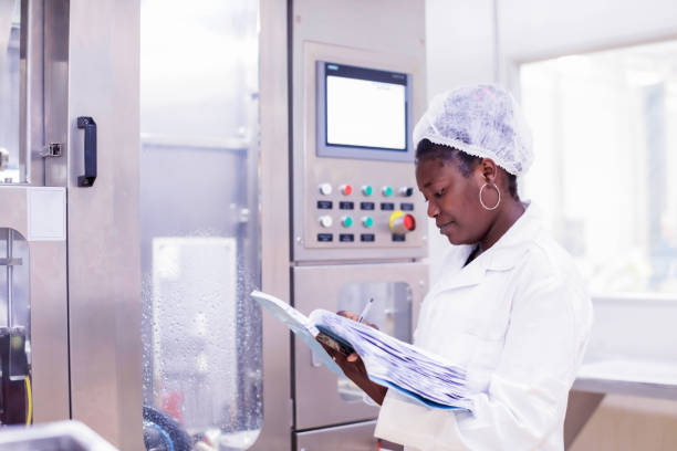Food Processing Plant Female Supervisor at Work Industry, Business, Production, Processing, Quality Control - Female Quality Inspector Taking Readings from the Machinery hair net stock pictures, royalty-free photos & images
