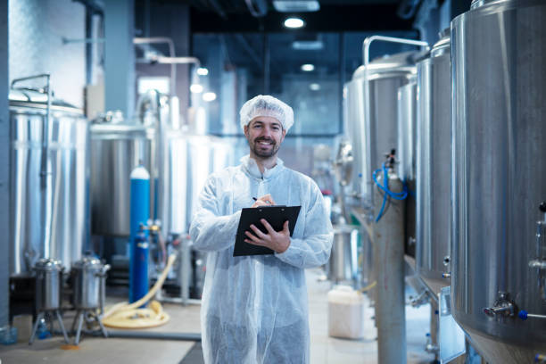 Food processing plant interior with positive smiling technologist holding checklist. Industrial worker satisfied with results and quality control. Food processing plant interior with positive smiling technologist holding checklist. Industrial worker satisfied with results and quality control. food warehouse stock pictures, royalty-free photos & images