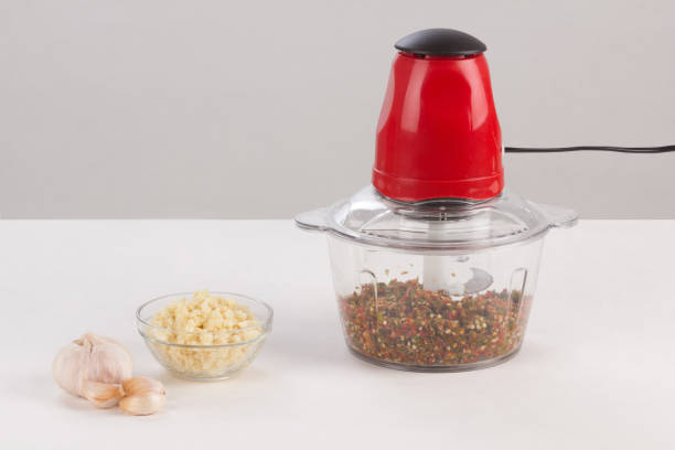 Food processor with chopped chilli inside isolated stock photo