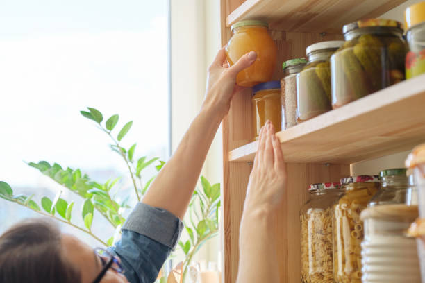 Mutfakta gıda ürünleri kiler içinde depolama malzemeleri. Kadın bal kavanozu alıyor stok fotoğrafı