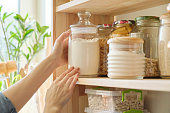 istock Food products in the kitchen. Woman taking jar of flour 1160739901