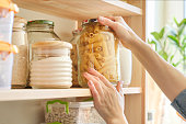 istock Food products in the kitchen. Woman taking jar of pasta 1160739664