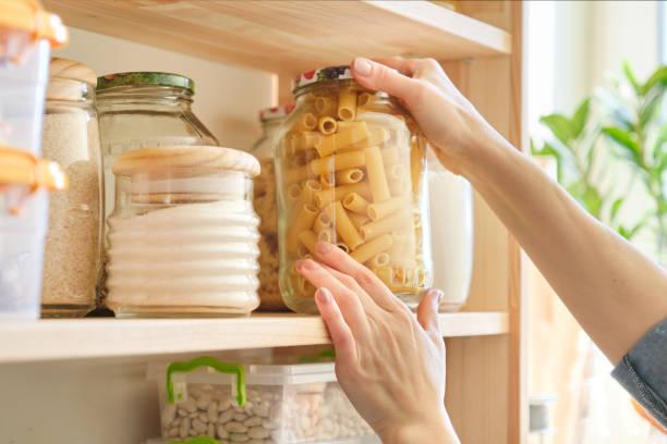Productos alimenticios en la cocina. Mujer tomando tarro de pasta - foto de stock