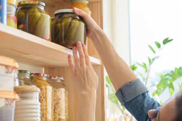 Productos alimenticios en la cocina, Mujer tomando tarro de pepinos encurtidos - foto de stock