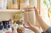istock Food products in the kitchen. Woman taking jar of rice 1160740403