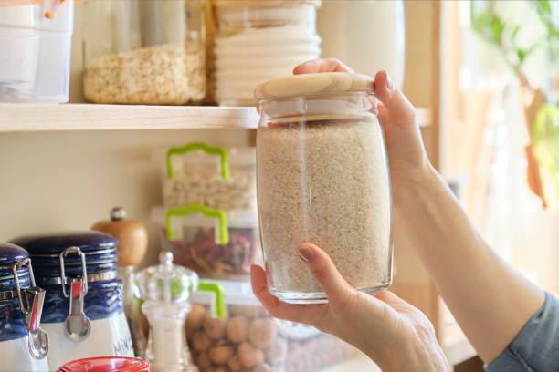 voedingsmiddelen in de keuken. vrouw met potje rijst - bloem stapelvoedsel stockfoto's en -beelden