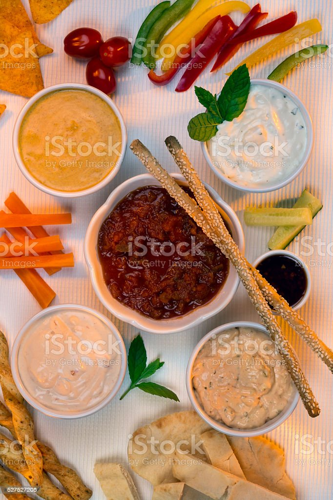 A selection of party dips with bread sticks, pita bread and other...