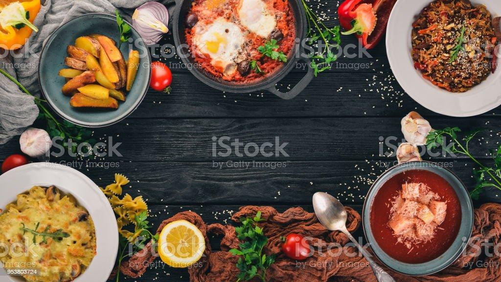 Alimentos. Conjunto de platos en la mesa. Sobre un fondo de madera. Vista superior. Copia espacio. - foto de stock