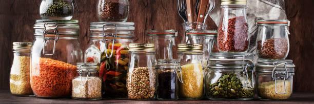 nahrungssatz. rohes getreide, nudeln, grütze, bio-hülsenfrüchte und nützliche samen in gläsern. vegane eiweiß-und energieressourcen. rustikal hölzerner küchentisch hintergrund. - grundnahrungsmittel stock-fotos und bilder