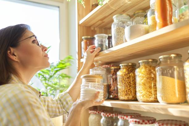 Food storage in pantry, woman holding jar of sugar in hand. Food storage in pantry, woman holding jar of sugar in hand. Pantry interior, wooden shelf with food cans and kitchen utensils domestic kitchen stock pictures, royalty-free photos & images