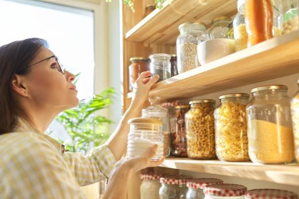 almacenamiento de alimentos en despensa, mujer sosteniendo tarro de azúcar en la mano. - arroz comida básica fotografías e imágenes de stock