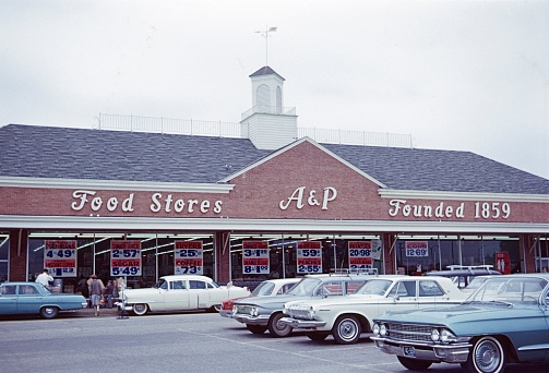 Washington DC, USA, 1964. A food store owned by A & P in Washington DC. Furthermore: parked cars, offers and consumers.
