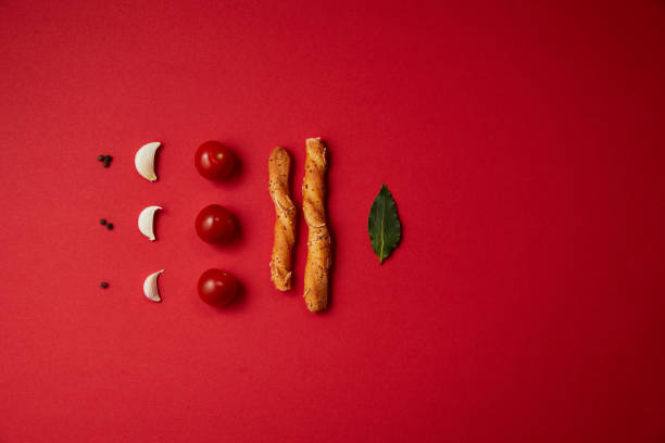 food styling of tasty tomatoes, garlic, bread sticks and bay leaf on red table - food styling stock photos and pictures