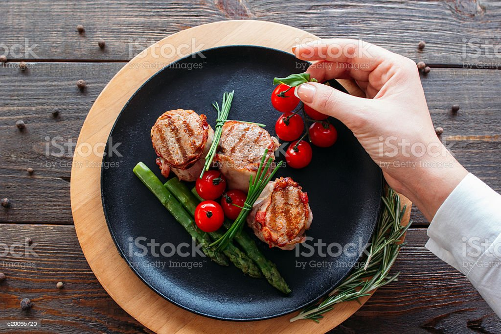 Food  stylist. Chef decorating a pork dish. stock photo