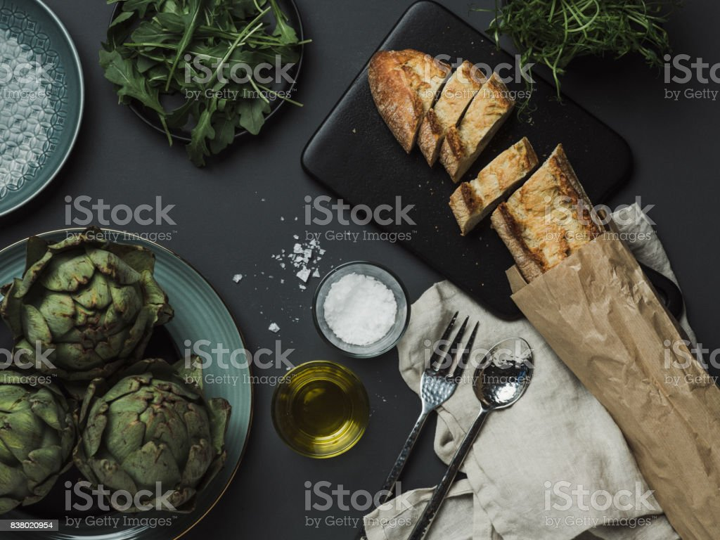 Food table setting with artichoke bread oils and salt stock photo