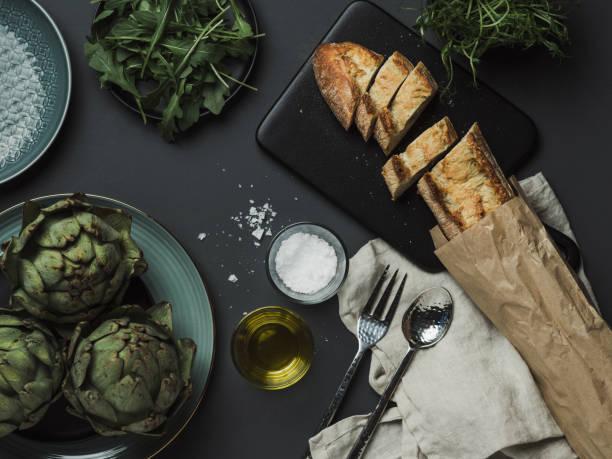 essen-tischdekoration mit artischocken-brot-öle und salz - speisesalz stock-fotos und bilder