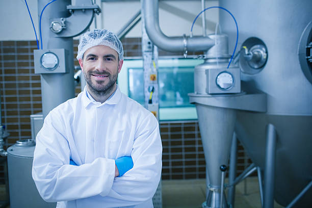 Food technician smiling at camera Food technician smiling at camera in a food processing plant hair net stock pictures, royalty-free photos & images