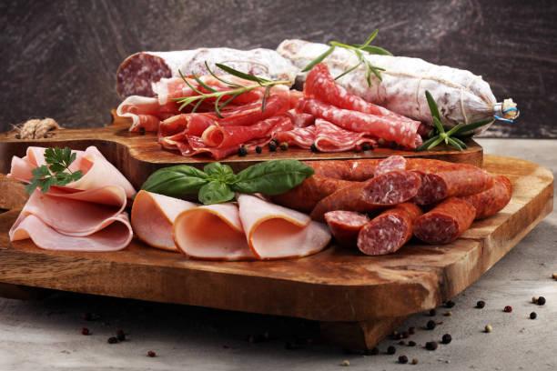 essbrett mit leckeren salami, schinken, frische würste und kräuter. fleischplatte mit auswahl - salami vorspeise stock-fotos und bilder