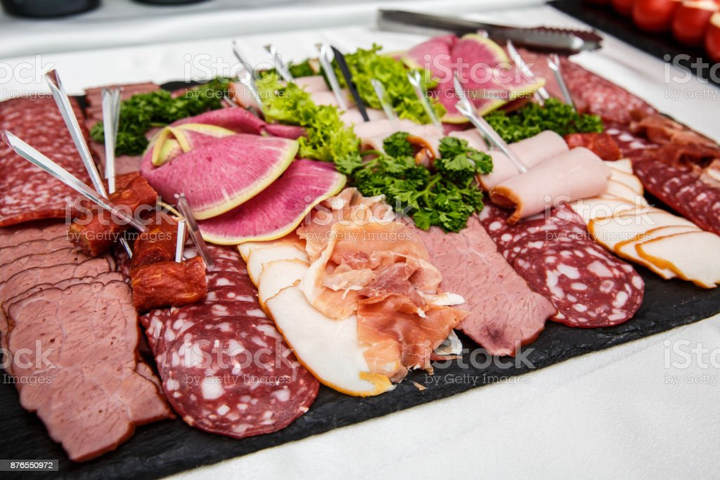 Food tray with delicious salami, pieces of sliced ham, sausage, salad - Meat platter with selection stock photo