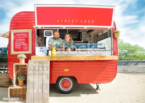 Red food truck  and owners, a young couple..