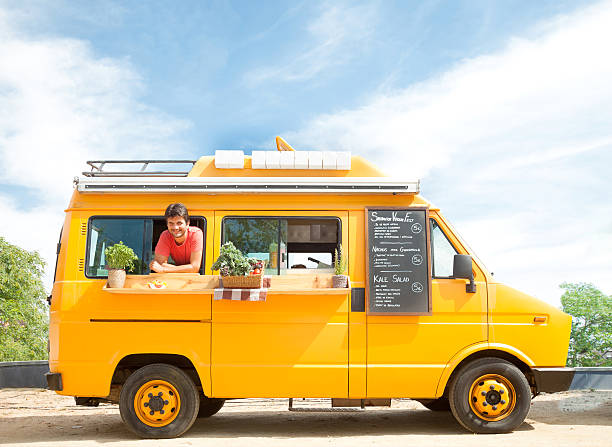 Food truck in the street Yellow food truck open and parked in the street, with owner. food truck stock pictures, royalty-free photos & images