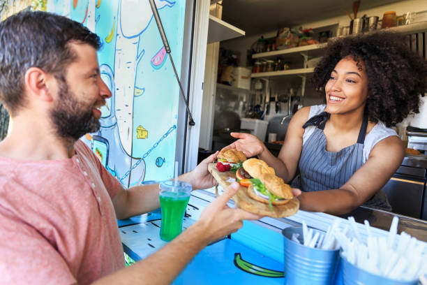 Food truck owner serving sandwiches to customer Female food truck worker serving sandwiches to customer. food truck stock pictures, royalty-free photos & images