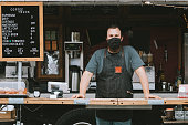 A mobile coffee truck is open for business during the Coronavirus pandemic.  The owner wears a mask during work hours.