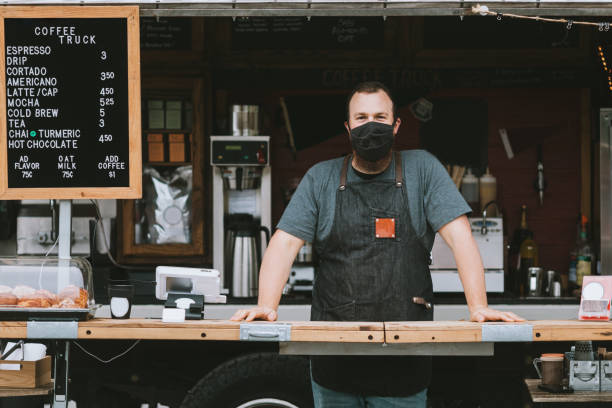 Food Truck Owner Wearing Protective Face Mask A mobile coffee truck is open for business during the Coronavirus pandemic.  The owner wears a mask during work hours. food truck stock pictures, royalty-free photos & images
