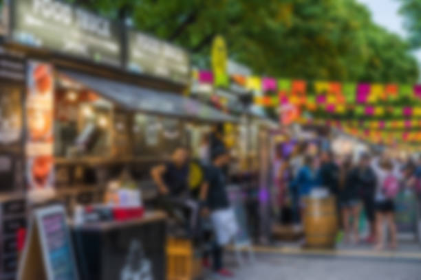 Food trucks and people at a street food market festival on a sunny day, blurred on purpose Food trucks and people at a street food market festival on a sunny day, blurred on purpose food festival stock pictures, royalty-free photos & images