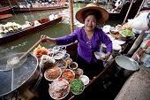 Food vendor at the Damnoen Saduak Floating Market preparing Thai style noodles, Thailand.
