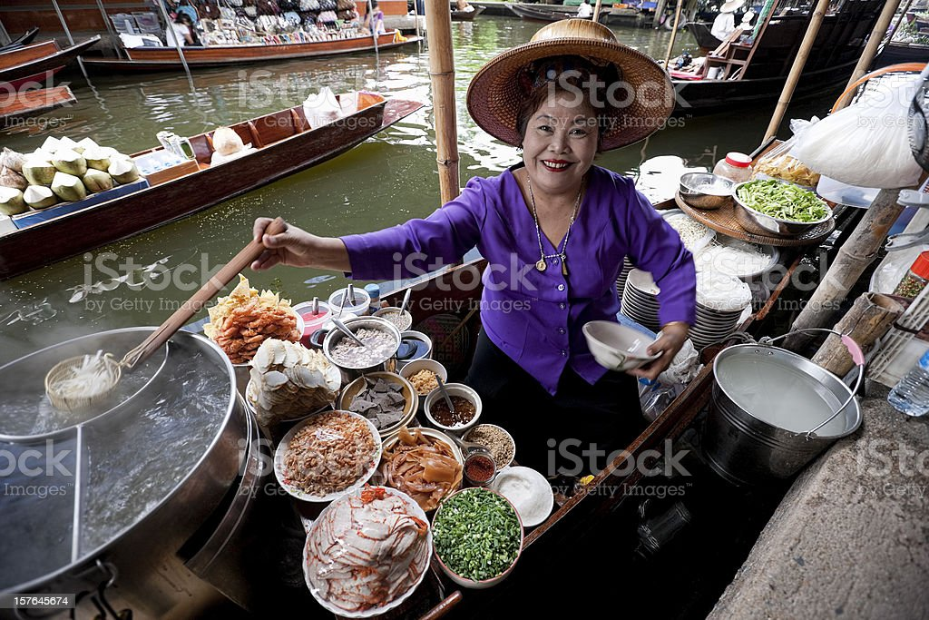 Food vendor at Damnoen Saduak Floating Market, Thailand. stock photo