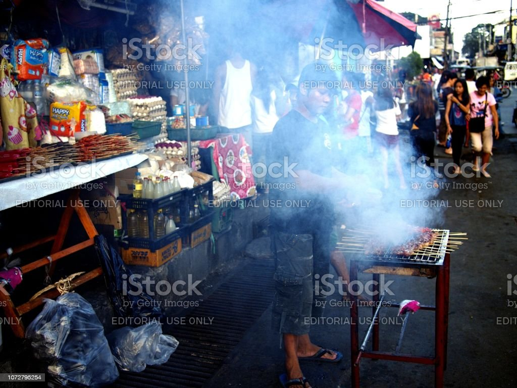 A food vendor grills pork barbecue and sells them at his makeshift stall stock photo