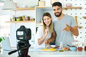 Closeup front view of a young couple taping a cooking video for their social media channel.
