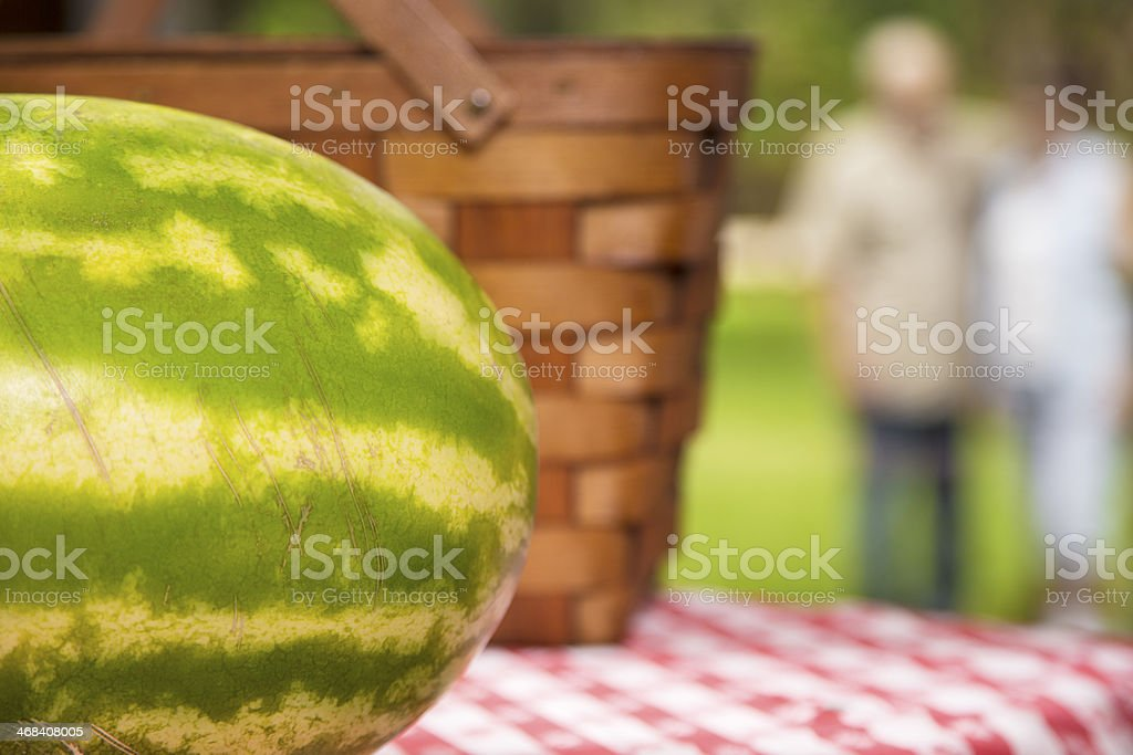 Food:  Watermelon on picnic table.  Senior couple in background. royalty-free stock photo