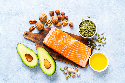 Healthy eating for well balanced diet and heart care: overhead view of a group of food rich in healthy fats. The composition includes salmon, avocado, extra virgin olive oil, nuts and seeds like walnut, almonds, pecan, hazelnuts, pistachio and pumpkin seeds. High resolution 42Mp studio digital capture taken with SONY A7rII and Zeiss Batis 40mm F2.0 CF lens
