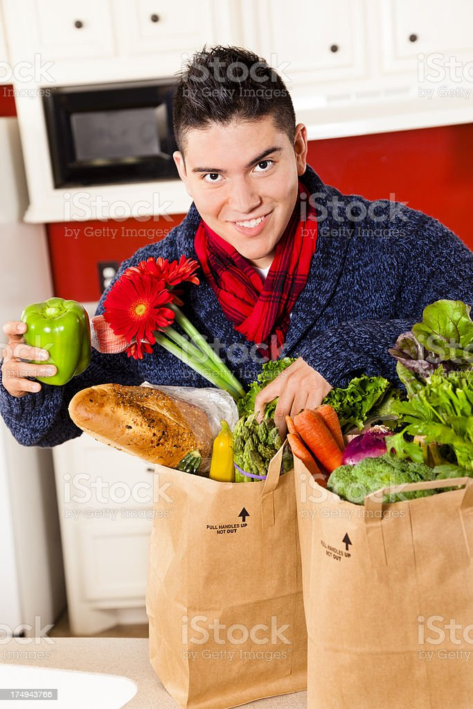Food:  Young Latin man in kitchen cheerfully unpacking groceries vegetables. royalty-free stock photo