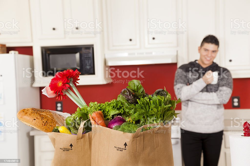 Food:  Young Latin man in kitchen drinking coffee groceries vegetables royalty-free stock photo