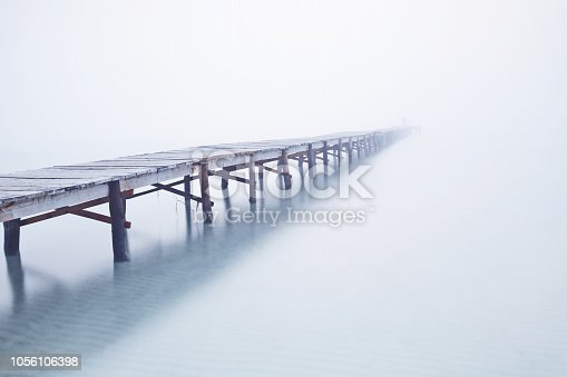 Foodbridge in the fog with a man standing on it