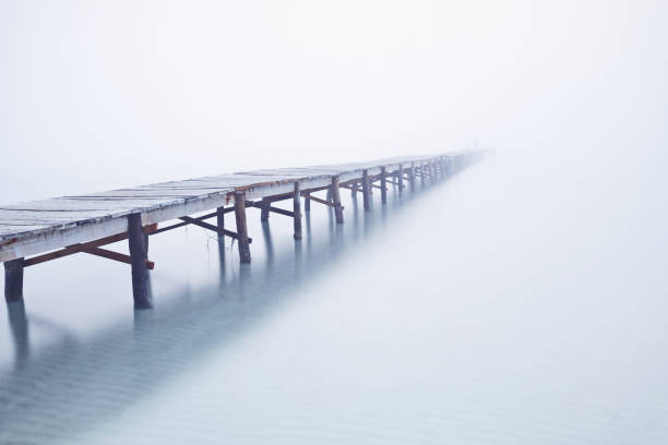 Foodbridge in the fog with a man standing on it Foodbridge in the fog with a man standing on it footbridge stock pictures, royalty-free photos & images