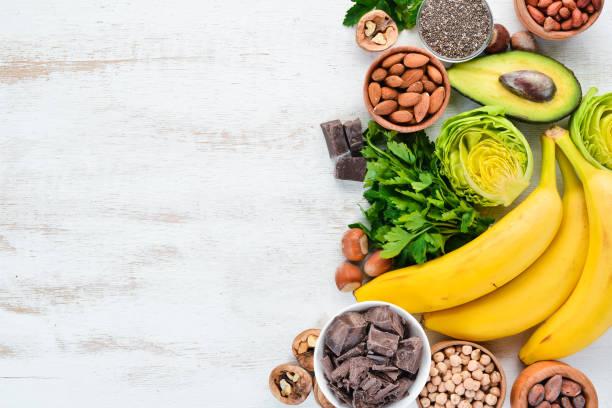 Alimentos contendo magnésio natural. Mg: chocolate, banana, cacau, nozes, abacates, brócolis, amêndoas. Vista superior. Em um fundo de madeira branco. - foto de acervo