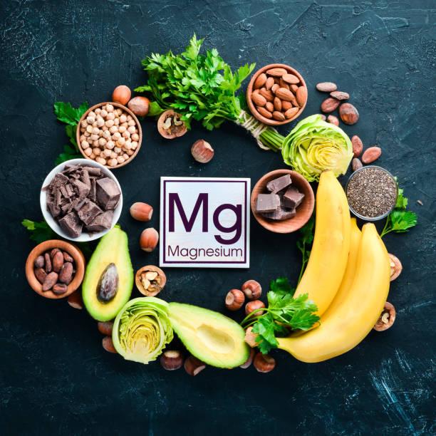 Alimentos contendo magnésio natural. Mg: chocolate, banana, cacau, nozes, abacates, brócolis, amêndoas. Vista superior. Em um fundo preto. - foto de acervo